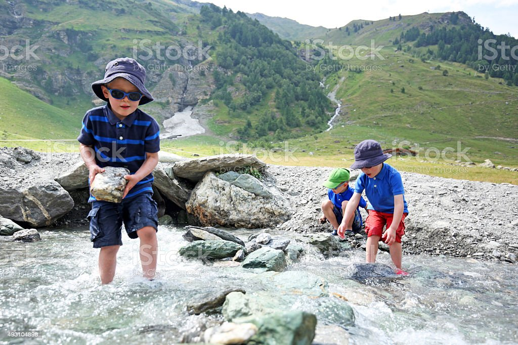 Children Building a River Dam in the Mountains in Switzerland stock photo
