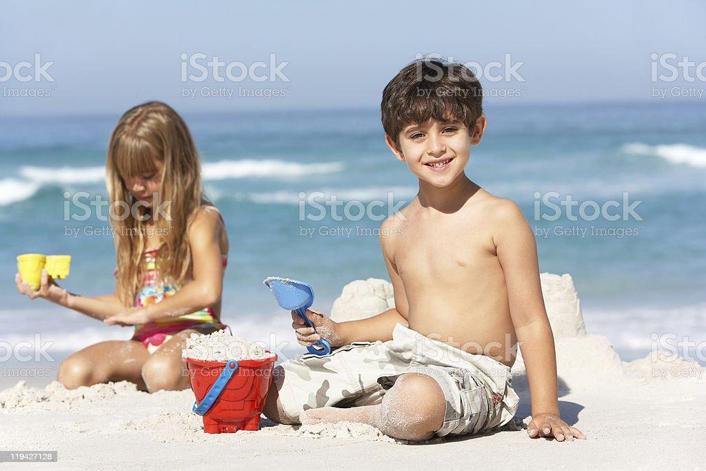 Children Building Sandcastles On Beach Holiday stock photo