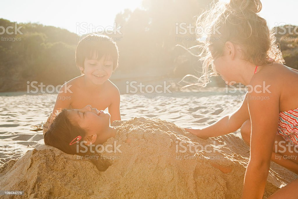 Children burying girl in sand stock photo