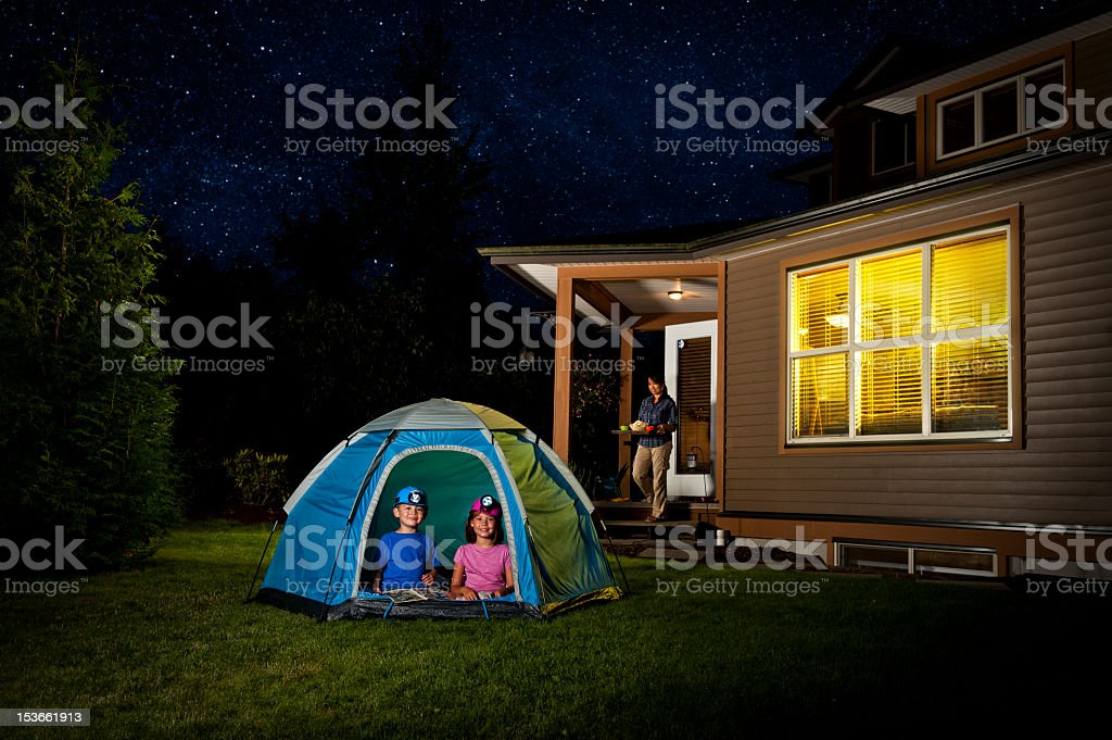 Children camping in a tent in the backyard stock photo