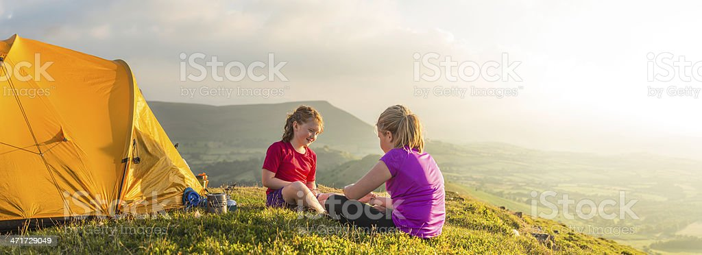 Children camping on green summer mountain overlooking sunlit valley panorama stock photo