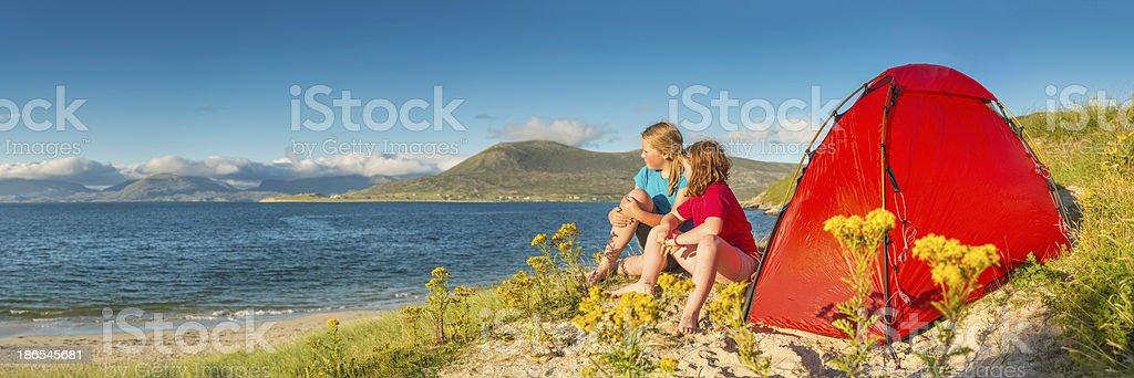 Children camping on idyllic golden beach dunes summer ocean panorama royalty-free stock photo