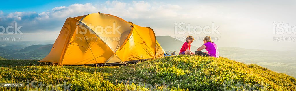Children camping on idyllic summer mountain top beside tent panorama stock photo