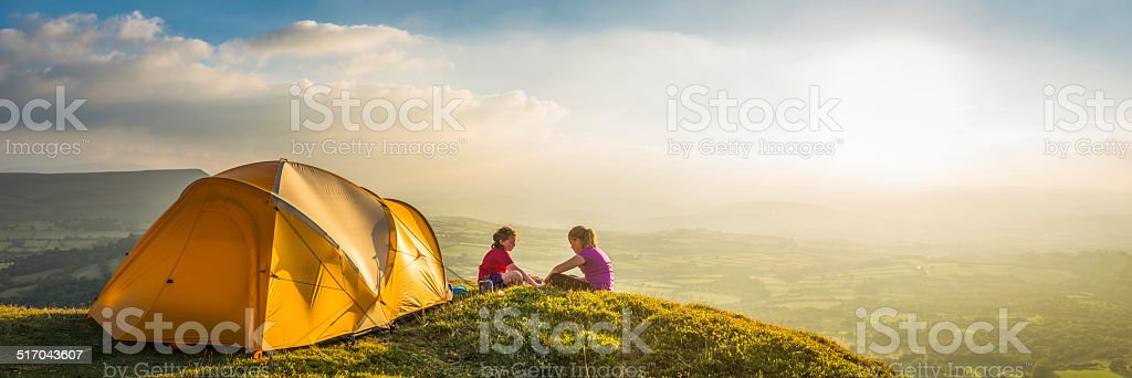 Children camping on idyllic summer sunset mountain light panorama stock photo