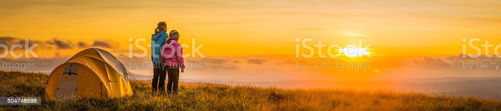 Children camping on mountain ridge looking into golden sunset panorama stock photo