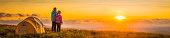 Children camping on mountain ridge looking into golden sunset panorama