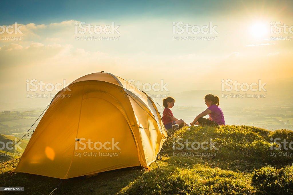 Children camping yellow tent on idyllic mountain top summer sunset stock photo