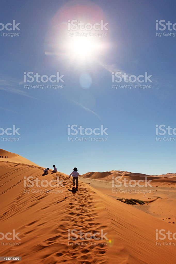 Children Climbing Red Sand Dunes in Sossusvlei Namibia stock photo