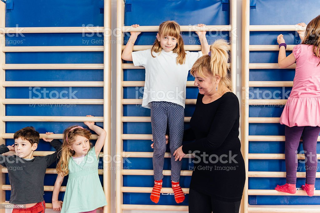 Children climbing wall bars stock photo