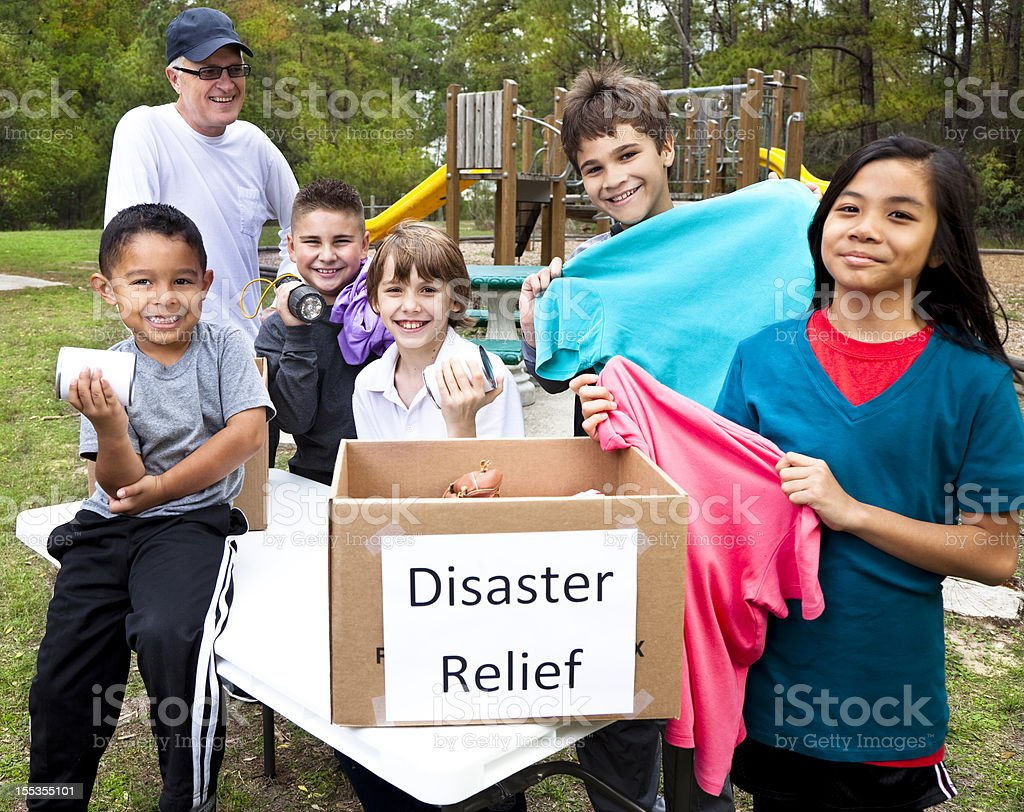 Children collecting donations for disaster relief victims. Park. Volunteers. stock photo
