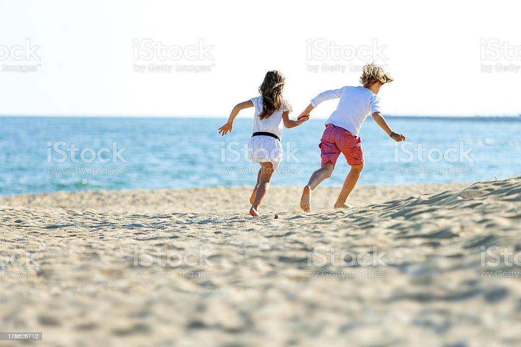 Enfants couple jogging sur la plage. photo libre de droits