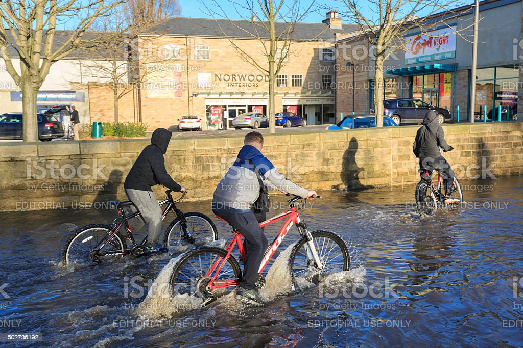 Children cycling on a flooded street past shops in Leeds stock photo