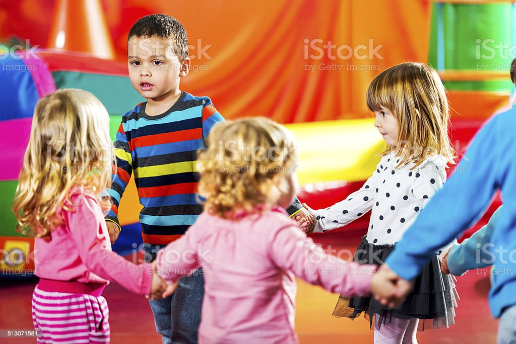 Children dancing in a playroom. stock photo