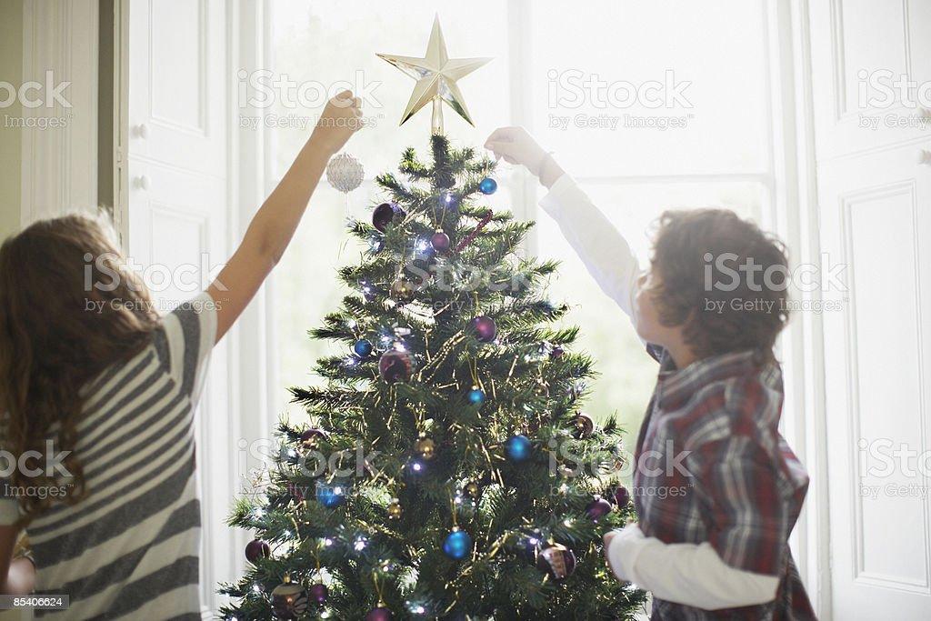 Children decorating Christmas tree stock photo