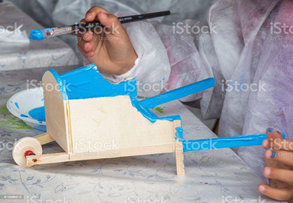 Children decorating handmade wooden handbarrow stock photo
