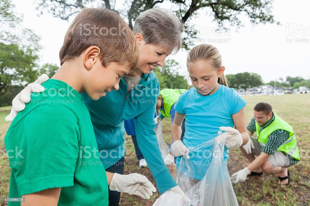 Children doing community service project with grandmother at park royalty-free stock photo