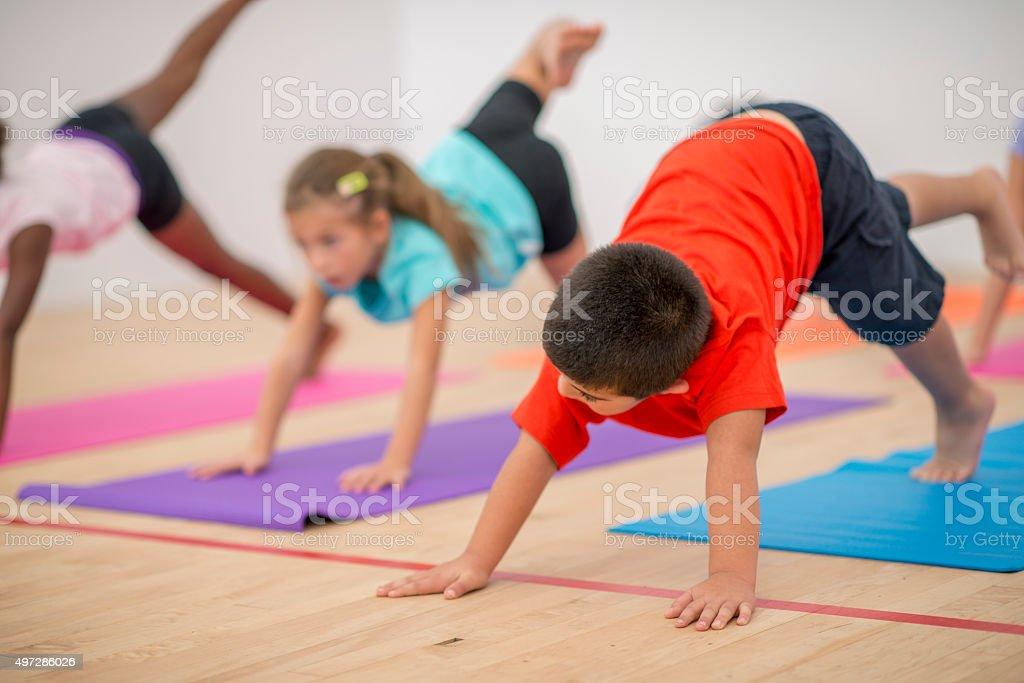 Children Doing Downward Dog Yoga Pose stock photo