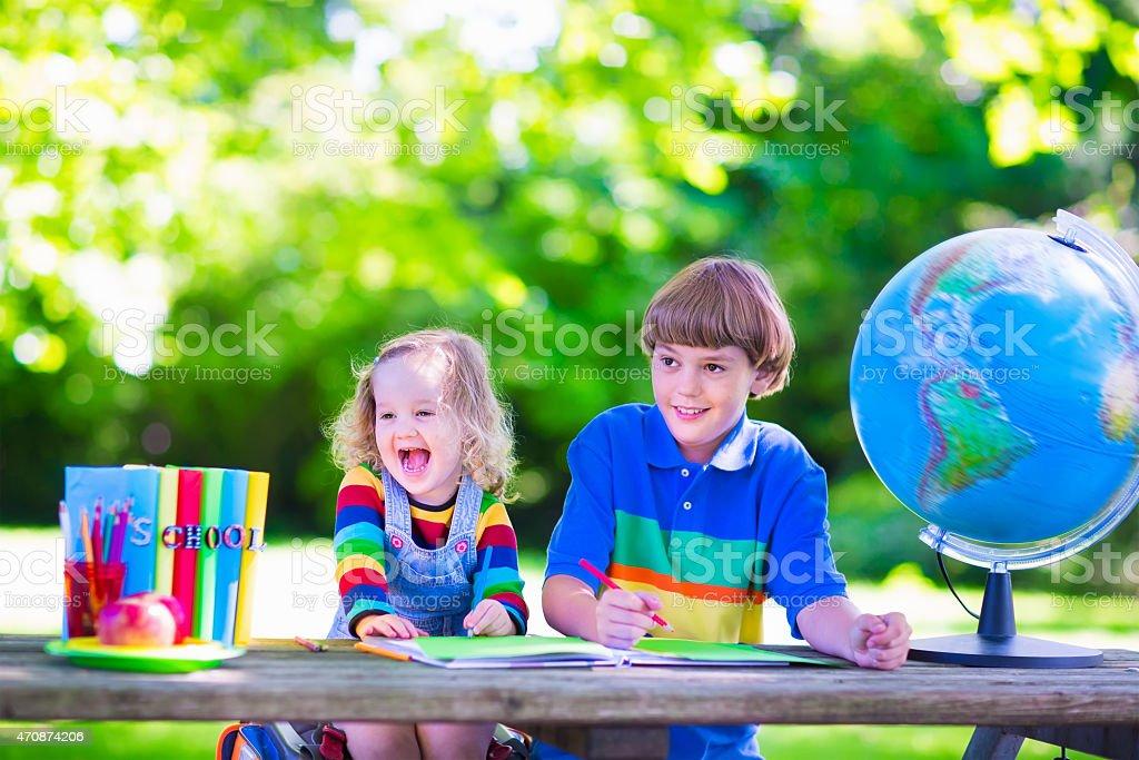 Children doing homework in school yard stock photo