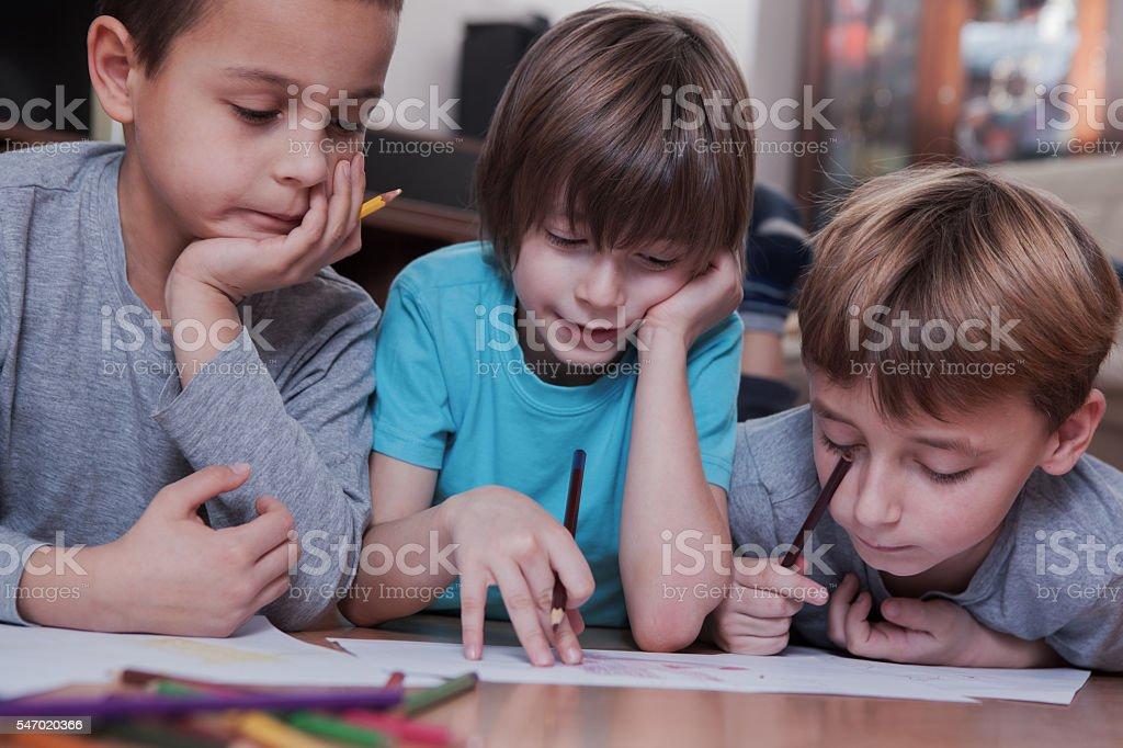 Children doing homework on the floor and having fun stock photo