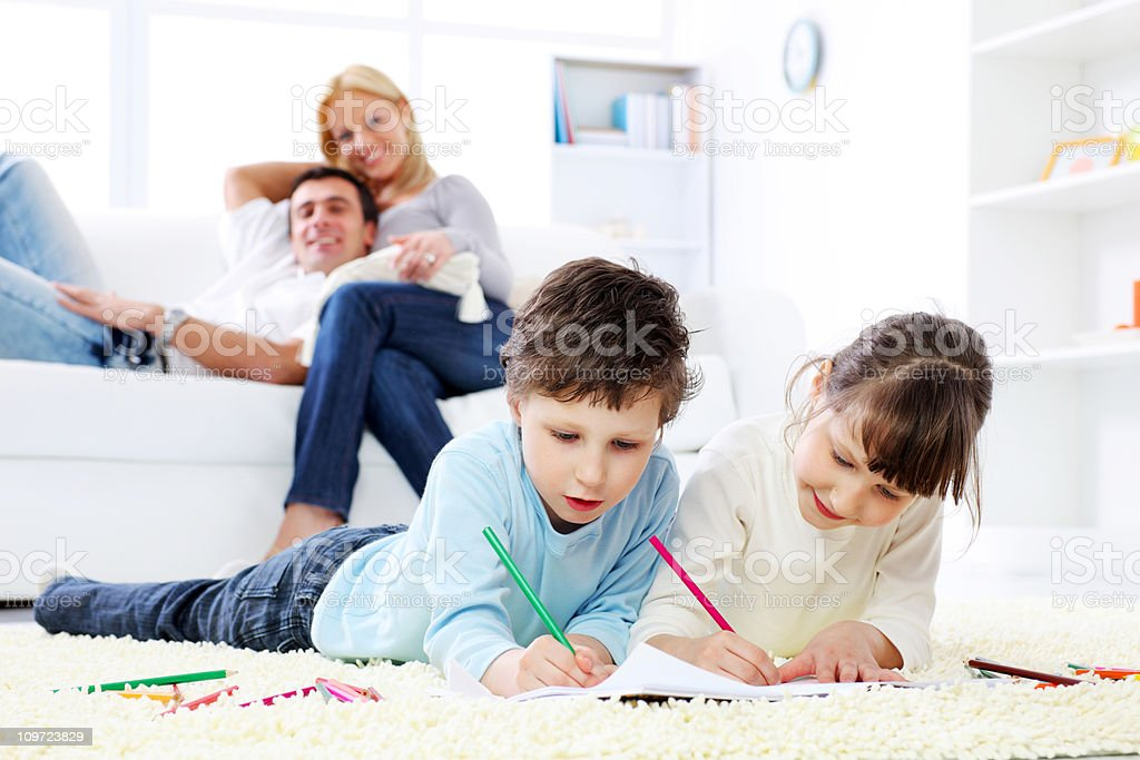 Children drawing in colorful pencils, hem parents on a backgroun royalty-free stock photo