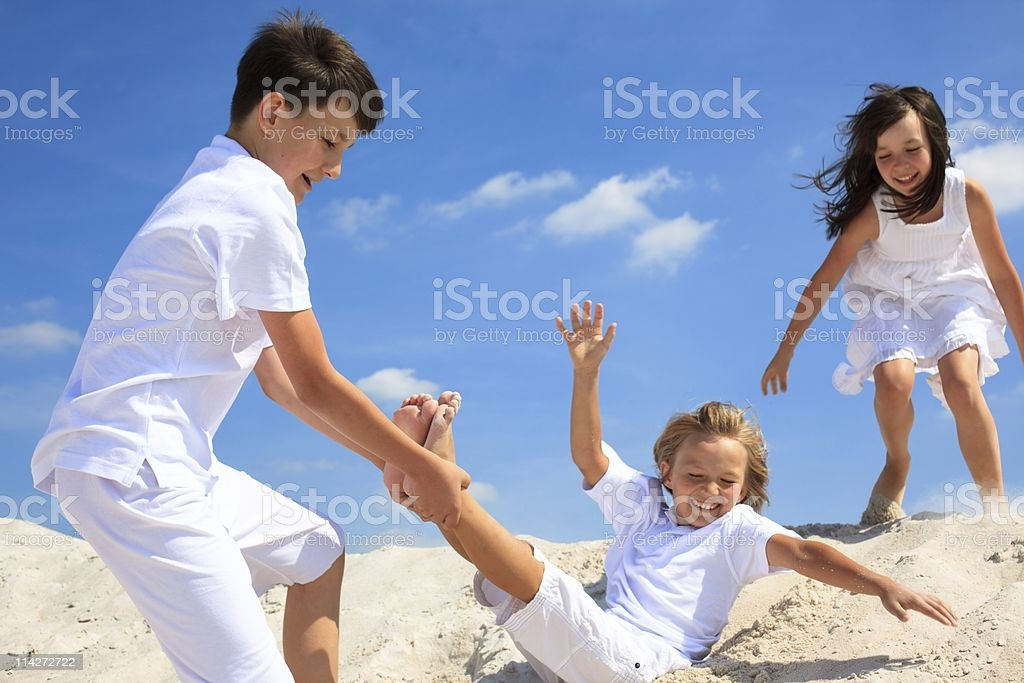 Children dressed in white playing on sandy beach royalty-free stock photo