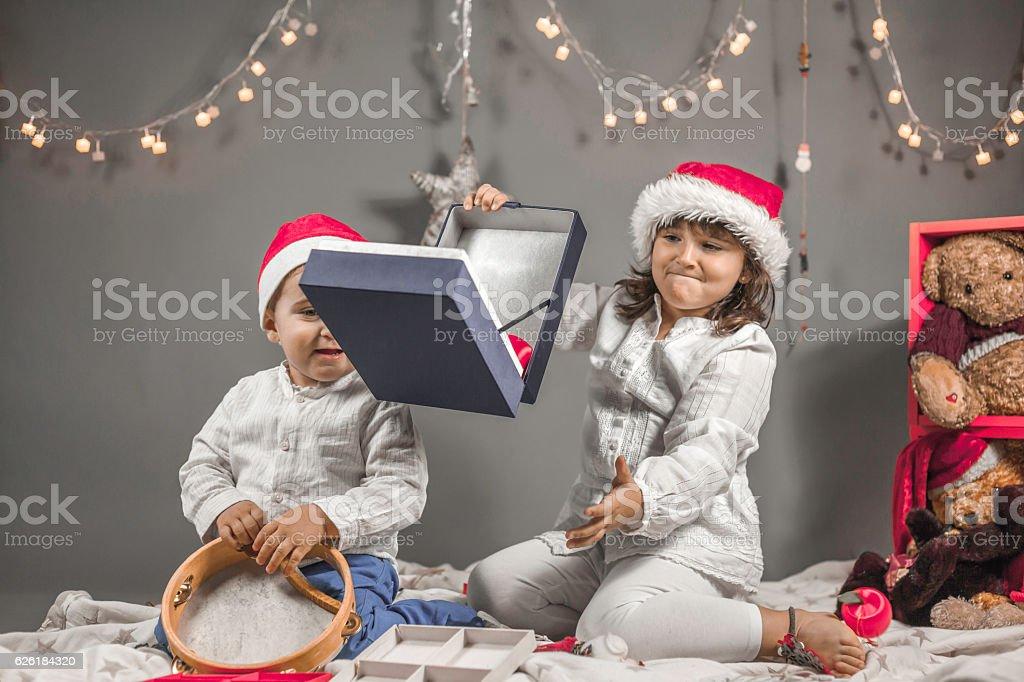 Children dressed with Santa hat, opening box, tambourine and Chr stock photo