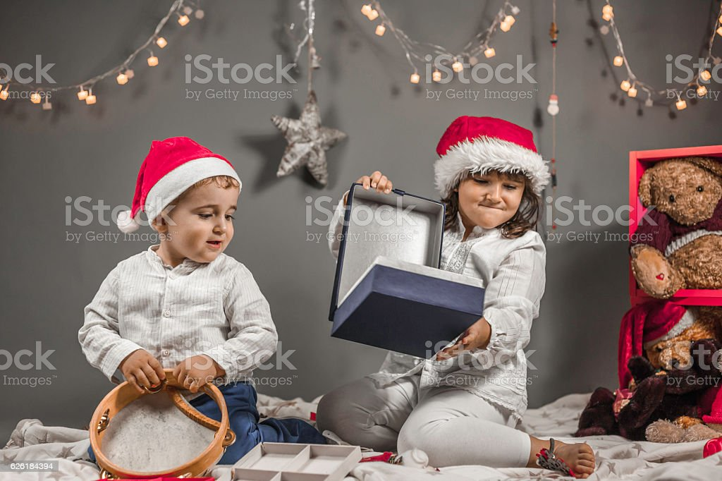 Children dressed with Santa hat, tambourine open box and Christm stock photo