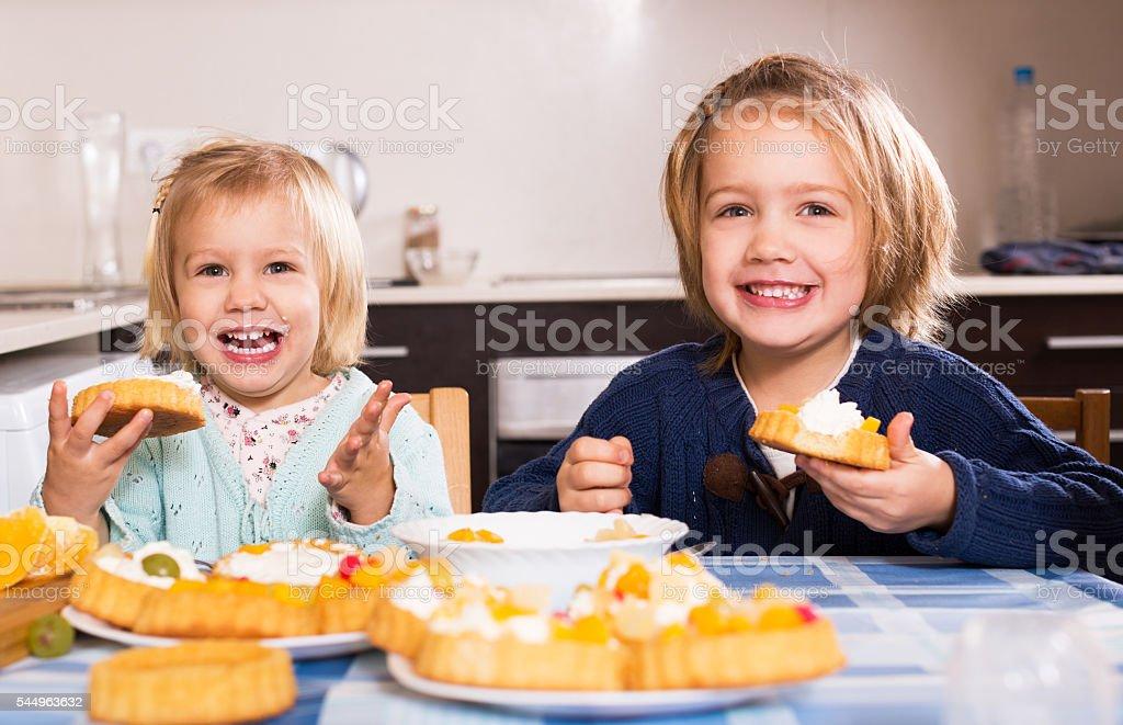 Children eat cakes at kitchen stock photo