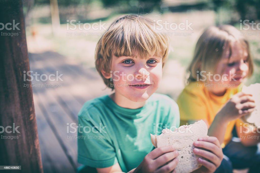 Children eating lunch on a porch step stock photo