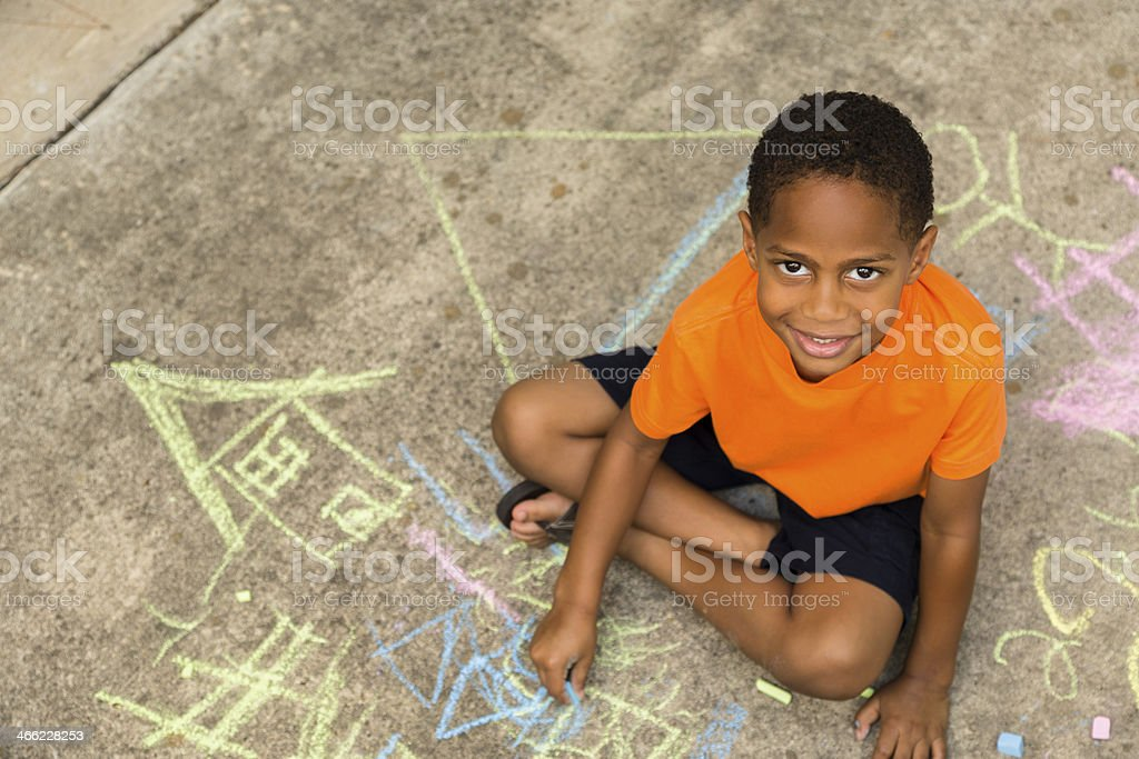 Children:  Elementary age African descent boy playing with sidewalk chalk. stock photo