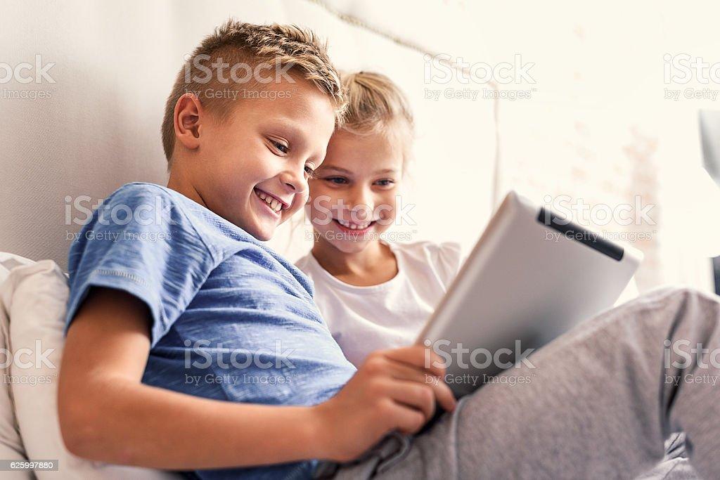 Children enjoying digital gadget in bedroom stock photo