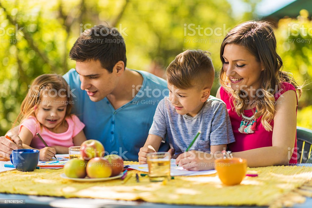 Children enjoying with parents in their garden and coloring together. stock photo