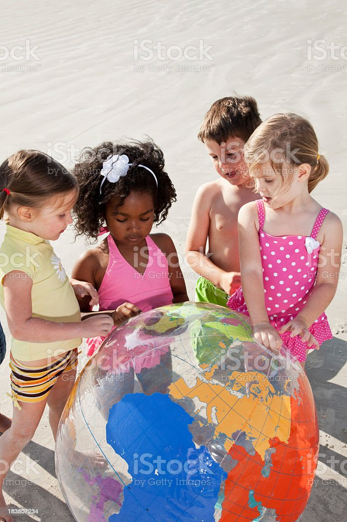 Children examining inflatable globe on beach royalty-free stock photo