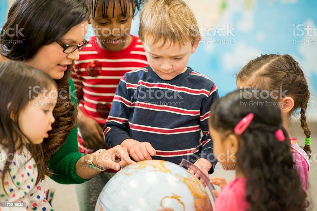 Children Exploring a Globe with Teacher stock photo