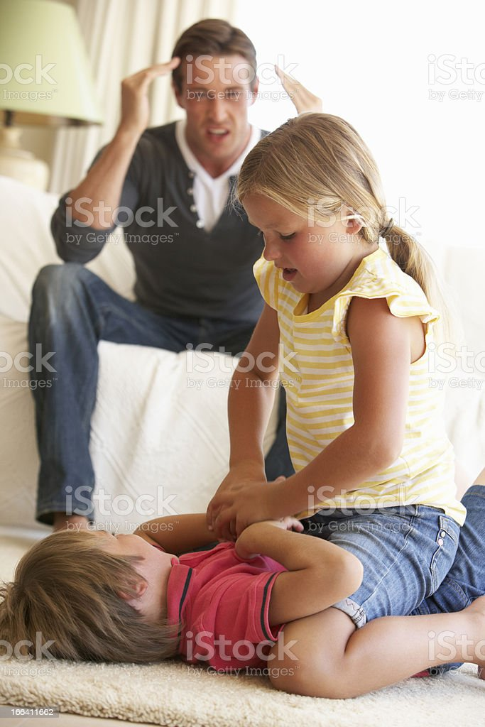 Children Fighting In Front Of Father At Home royalty-free stock photo