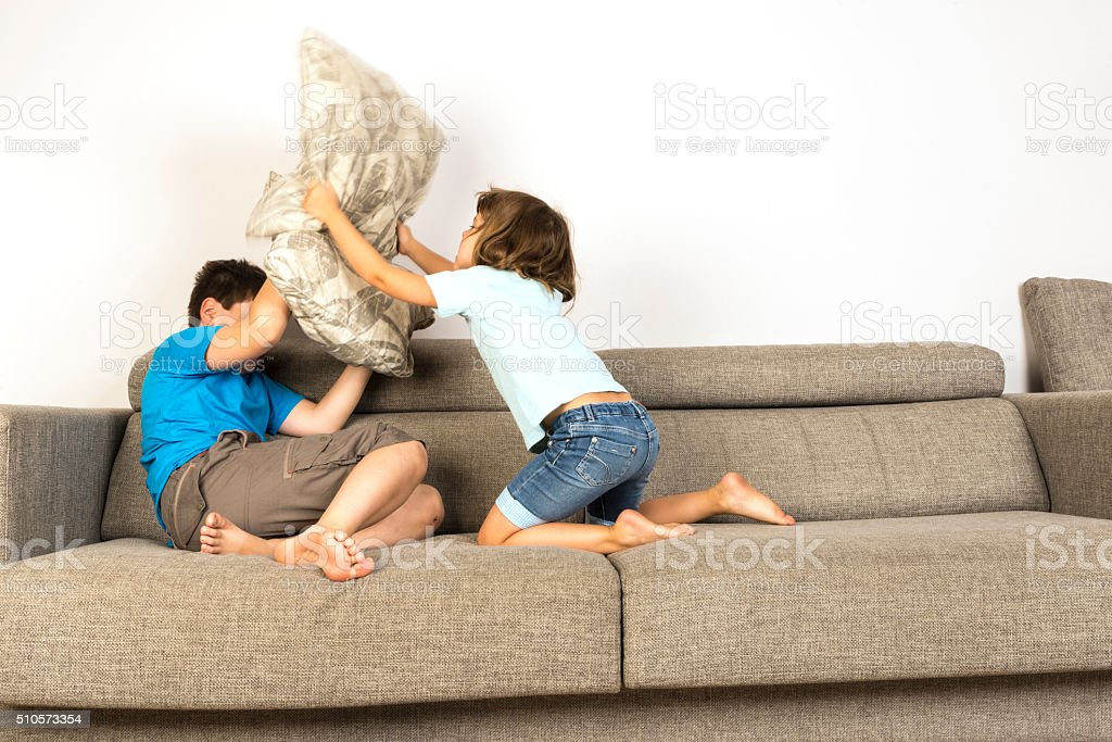Children fighting together with pillows stock photo