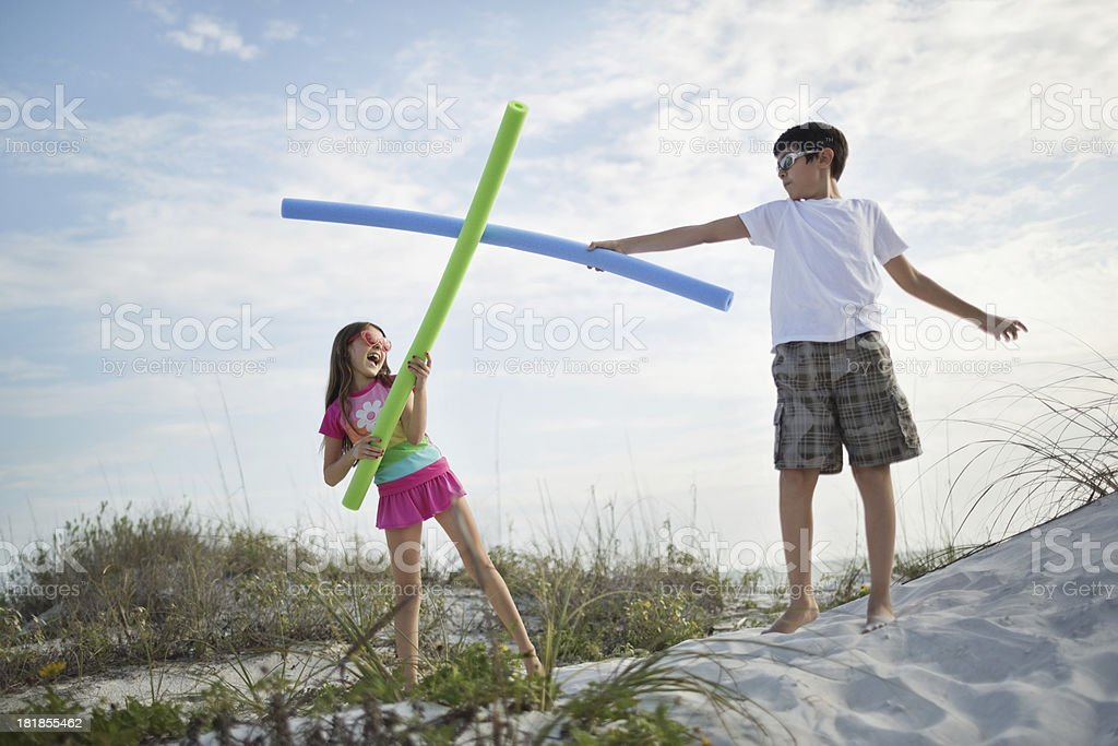Children Fighting With Pool Noodles On Beach royalty-free stock photo