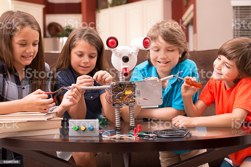 Children friends build robot together at home. stock photo