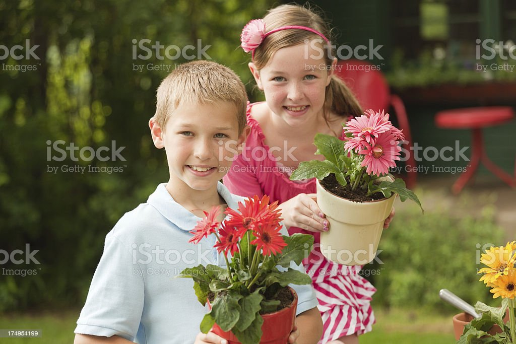 Children Gardening and Planting Flowers Together Hz royalty-free stock photo