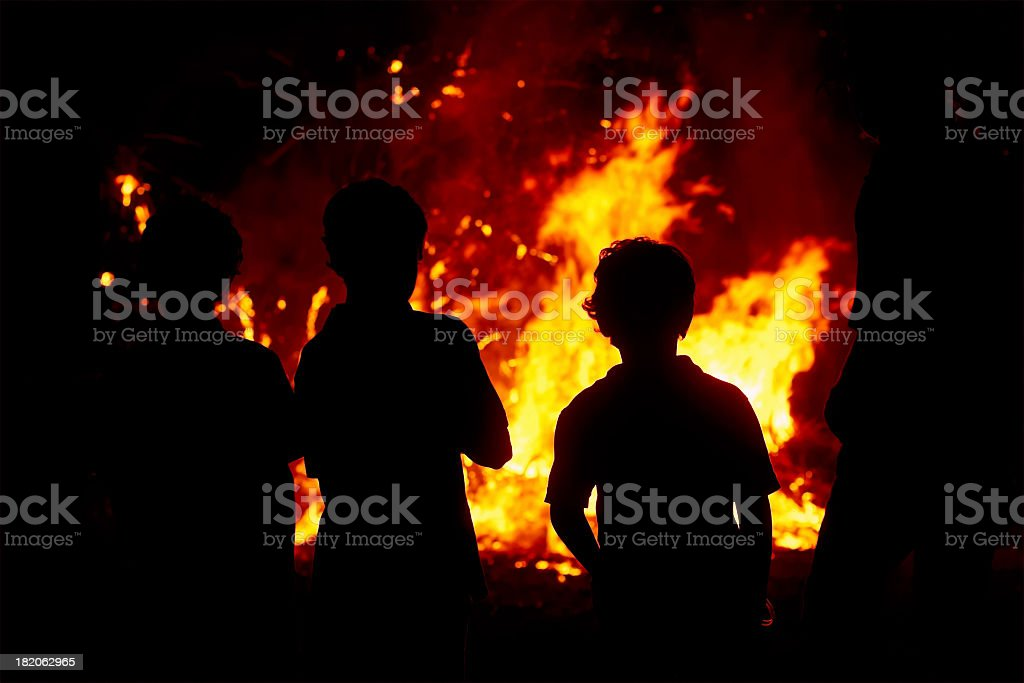 Children gazing at a raging bonfire in the dark stock photo