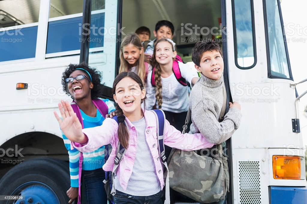 Children getting on school bus stock photo
