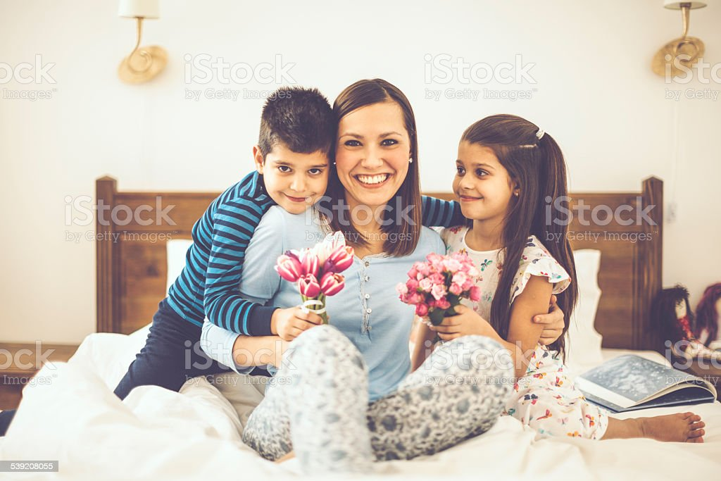 Children giving flowers to their mother on the Mother's day stock photo