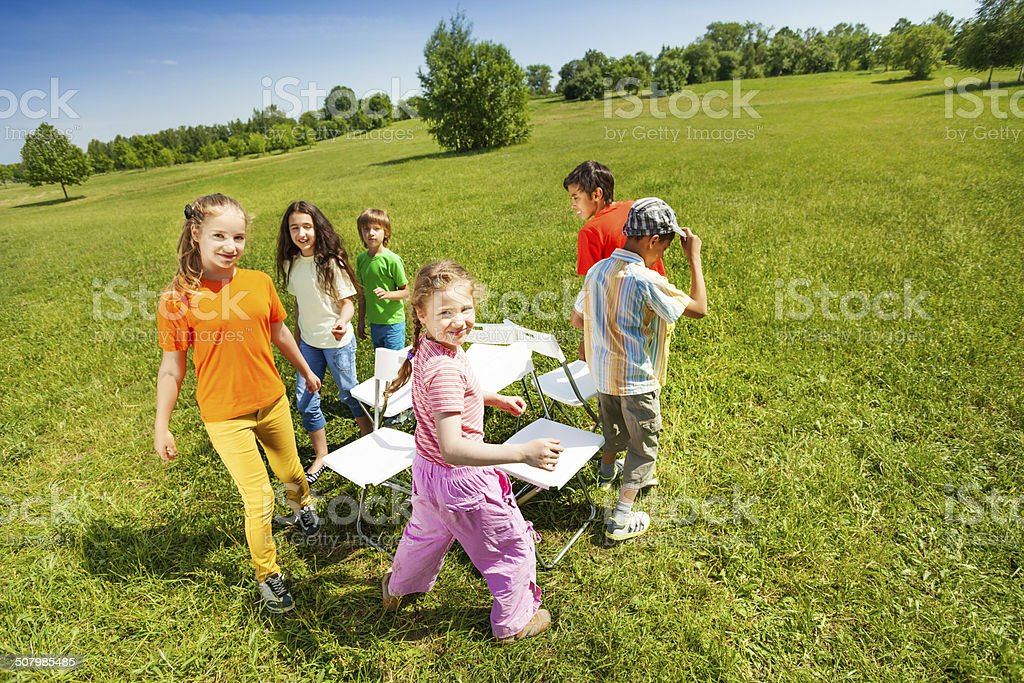 Children go around playing musical chairs outside stock photo