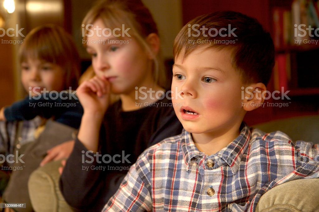 children group watching tv, focus at the boy in front royalty-free stock photo