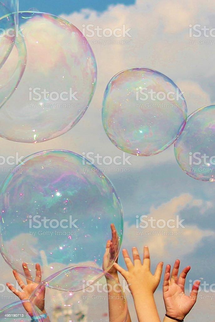 children hands reach for bubble stock photo