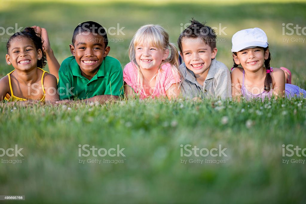 Children Happily Sitting on a Grassy Hill stock photo