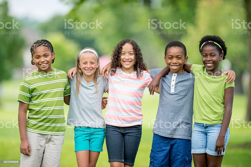 Children Happily Standing Together at the Park stock photo