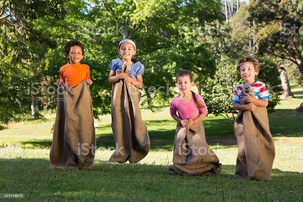 Children having a sack race in park stock photo