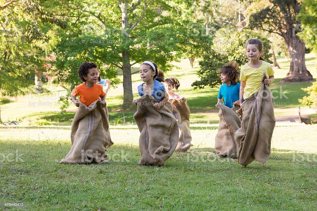 Children having a sack race in park stock photo