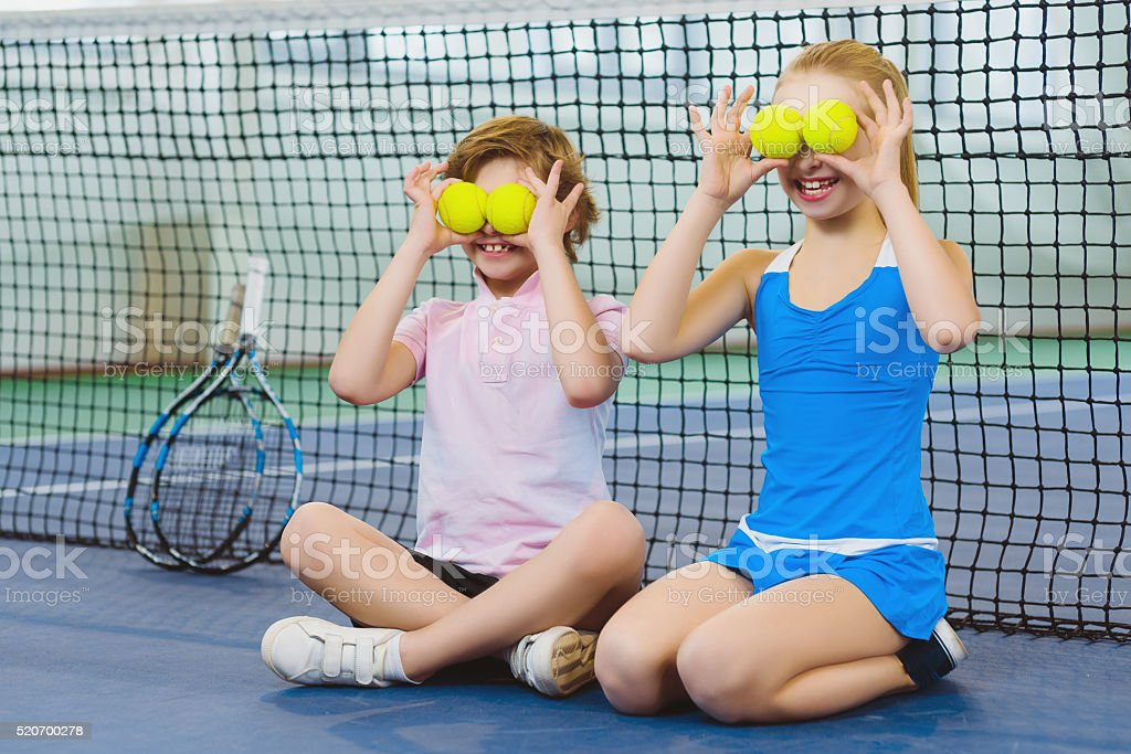 children having fun and playing on the tennis court stock photo